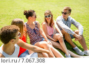 Купить «group of smiling friends outdoors sitting in park», фото № 7067308, снято 20 июля 2014 г. (c) Syda Productions / Фотобанк Лори