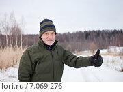 Купить «Пожилой мужчина на зимней прогулке поднимает большой палец руки вверх», фото № 7069276, снято 24 февраля 2015 г. (c) Victoria Demidova / Фотобанк Лори