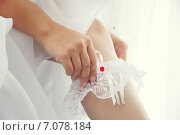 Невеста со свадебным маникюром надевает подвязку на ногу. Стоковое фото, фотограф Ксения Богданова / Фотобанк Лори