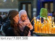 Купить «Молодая женщина с дочерью ставят свечку в православной церкви», фото № 7091508, снято 2 мая 2014 г. (c) EugeneSergeev / Фотобанк Лори