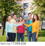 Купить «group of smiling teenagers over campus background», фото № 7094636, снято 22 июня 2014 г. (c) Syda Productions / Фотобанк Лори