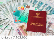 Пенсионное удостоверение, социальная карта на фоне из денежных банкнот (2015 год). Редакционное фото, фотограф Сергей Кочевых / Фотобанк Лори