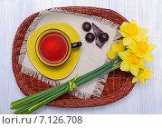 Чашка чая, шоколад и нарциссы на плетенном подносе. Стоковое фото, фотограф Marina Kutukova / Фотобанк Лори