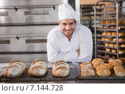 Купить «Happy baker standing near tray with bread», фото № 7144728, снято 8 сентября 2014 г. (c) Wavebreak Media / Фотобанк Лори