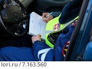 Купить «Сотрудник ГИБДД, сидя в машине, выписывает штраф за нарушение правил дорожного движения», эксклюзивное фото № 7163560, снято 20 марта 2015 г. (c) Яна Королёва / Фотобанк Лори
