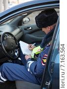 Купить «Сотрудник ГИБДД сидя в машине выписывает штраф за нарушение правил дорожного движения», эксклюзивное фото № 7163564, снято 20 марта 2015 г. (c) Яна Королёва / Фотобанк Лори