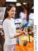 Купить «happy woman with basket and tablet pc in market», фото № 7179064, снято 20 декабря 2014 г. (c) Syda Productions / Фотобанк Лори