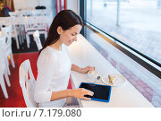 Купить «smiling woman with tablet pc and coffee at cafe», фото № 7179080, снято 20 декабря 2014 г. (c) Syda Productions / Фотобанк Лори
