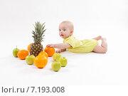 Ребенок лежит на белом фоне среди фруктов. Стоковое фото, фотограф Иван Траймак / Фотобанк Лори