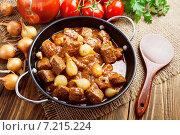 Купить «Мясо, тушенное с томатной пастой и луком, в сковороде на столе», фото № 7215224, снято 31 марта 2015 г. (c) Надежда Мишкова / Фотобанк Лори