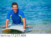 Купить «Сёрфингист на пляже с доской для серфинга», фото № 7217404, снято 25 мая 2020 г. (c) Максим Топчий / Фотобанк Лори