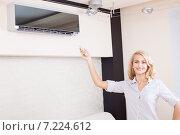 Female holding a remote control air conditioner. Стоковое фото, фотограф Гладских Татьяна / Фотобанк Лори