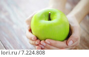 Купить «close up of young woman hands showing green apple», видеоролик № 7224808, снято 20 марта 2015 г. (c) Syda Productions / Фотобанк Лори