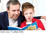 Папа и сын читают книгу. Стоковое фото, фотограф Данил Руденко / Фотобанк Лори