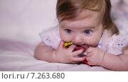 Грудная девочка улыбается и грызёт яркую погремушку, лежа на животе. Стоковое видео, видеограф Потийко Сергей / Фотобанк Лори