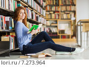 happy student girl reading book in library. Стоковое фото, фотограф Syda Productions / Фотобанк Лори