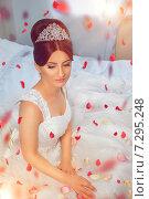 Купить «Красивая невеста с лепестками роз сидит, опустив глаза», фото № 7295248, снято 20 июня 2014 г. (c) Emelinna / Фотобанк Лори