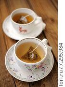 Купить «Пирамидальные пакетики с зелёным чаем в двух светлых чашках», фото № 7295984, снято 20 июля 2014 г. (c) Алексей Бородин / Фотобанк Лори