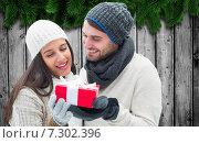 Купить «Composite image of winter couple holding gift», фото № 7302396, снято 25 июня 2019 г. (c) Wavebreak Media / Фотобанк Лори
