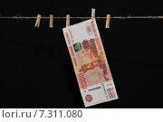 Купюра номиналом 5000 рублей висит на миниатюрной прищепке. Стоковое фото, фотограф Константин Пекарь / Фотобанк Лори