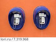 Телефоны-автоматы висят на оранжевой стене. Стоковое фото, фотограф Мячикова Наталья / Фотобанк Лори
