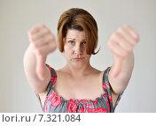 Купить «Разочарованная женщина показывает жест большой палец вниз двумя руками», фото № 7321084, снято 25 апреля 2015 г. (c) Володина Ольга / Фотобанк Лори