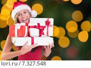 Купить «Smiling young woman in santa hat holding a gift», фото № 7327548, снято 10 июля 2020 г. (c) Wavebreak Media / Фотобанк Лори