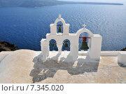 Купить «View on calm Sea Surface through traditional Greek white church, arch with cross, and bells. Village Oia, Crete, Cyclades Island», фото № 7345020, снято 18 января 2020 г. (c) BE&W Photo / Фотобанк Лори