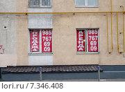 Купить «Аренда и продажа. Баннеры в окнах здания. Москва», эксклюзивное фото № 7346408, снято 26 апреля 2015 г. (c) Илюхина Наталья / Фотобанк Лори