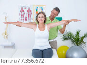 Купить «Doctor stretching his patients arms», фото № 7356672, снято 16 января 2015 г. (c) Wavebreak Media / Фотобанк Лори