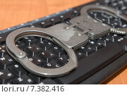 Купить «Наручники лежат на компьютерной клавиатуре», фото № 7382416, снято 24 апреля 2015 г. (c) Pukhov K / Фотобанк Лори