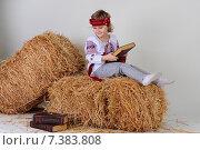 Девочка в украинской национальной одежде сидит на сене с книгой в руках. Стоковое фото, фотограф Olena Kravchuk / Фотобанк Лори