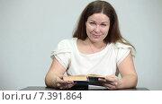 Купить «Молодая женщина улыбается в камеру во время чтения книги за столом», видеоролик № 7391864, снято 4 марта 2015 г. (c) Кекяляйнен Андрей / Фотобанк Лори