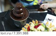 Дети едят фрукты, обмакивая их в шоколадном фонтане. Стоковое видео, видеограф Кекяляйнен Андрей / Фотобанк Лори