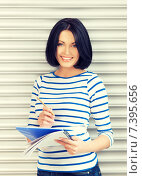 Купить «happy and smiling teenage girl with big notepad», фото № 7395656, снято 7 апреля 2012 г. (c) Syda Productions / Фотобанк Лори