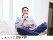 Купить «young man watching tv and eating popcorn at home», фото № 7399780, снято 15 марта 2014 г. (c) Syda Productions / Фотобанк Лори