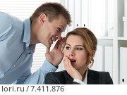 Купить «Сплетни в офисе. Молодой мужчина шепчет на ухо что-то удивленной деловой женщине», фото № 7411876, снято 27 апреля 2015 г. (c) Людмила Дутко / Фотобанк Лори