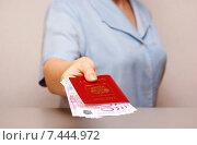 Купить «Женщина протягивает заграничный паспорт РФ с вложенными купюрами евро (фокус на деньгах)», фото № 7444972, снято 17 мая 2015 г. (c) Анна Менщикова / Фотобанк Лори