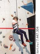 Купить «Девочка скалолаз висит на страховочной веревке, альпинизм в зале», фото № 7447304, снято 23 февраля 2015 г. (c) Кекяляйнен Андрей / Фотобанк Лори