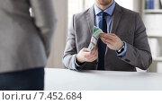 Купить «close up of businessman taking money bribe», видеоролик № 7452684, снято 12 апреля 2015 г. (c) Syda Productions / Фотобанк Лори