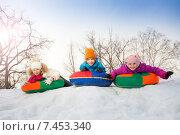 Трое детей лежат на разноцветных ватрушках на снежной горке зимой. Стоковое фото, фотограф Сергей Новиков / Фотобанк Лори