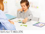 Купить «Дошкольник. Мальчик сидит за столом перед воспитателем и раскладывает карточки», фото № 7463376, снято 15 марта 2015 г. (c) Сергей Новиков / Фотобанк Лори