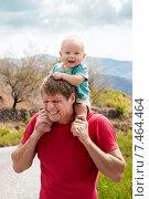Ребенок сидит на плечах у папы и держит его за волосы. Стоковое фото, фотограф Maria Siurtukova / Фотобанк Лори