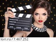 Купить «Молодая модная брюнетка в вечернем черном платье с хлопушкой на темном фоне», фото № 7467252, снято 29 мая 2014 г. (c) Photobeauty / Фотобанк Лори