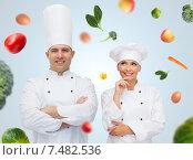 Купить «happy chef couple or cooks over food background», фото № 7482536, снято 7 марта 2015 г. (c) Syda Productions / Фотобанк Лори