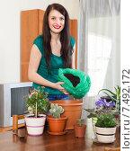 Smiling girl working with flowers in pots. Стоковое фото, фотограф Яков Филимонов / Фотобанк Лори