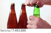 Купить «Мужчина пытается открутить крышку зеленой пивной бутылки», видеоролик № 7493888, снято 19 мая 2015 г. (c) Кекяляйнен Андрей / Фотобанк Лори