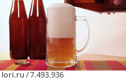 Купить «Нефильтрованное пиво из темной пивной бутылки доливается в большую стеклянную кружку на столе», видеоролик № 7493936, снято 19 мая 2015 г. (c) Кекяляйнен Андрей / Фотобанк Лори