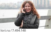 Купить «Довольная молодая женщина разговаривает по мобильному телефону на улице», видеоролик № 7494148, снято 5 мая 2015 г. (c) Кекяляйнен Андрей / Фотобанк Лори