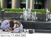 Мужчины ремонтируют городской фонтан (2015 год). Редакционное фото, фотограф demon15 / Фотобанк Лори